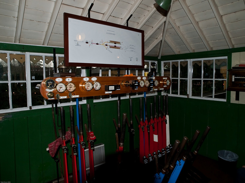 Alresford Signal Box. Copyright 2009 Peter Drury<br /> A general view of the lever frame and indicators. The red levers are to operate the signals, the blue levers operate the points, the black levers operate the catch points and the white lever is a spare. The dials abobe the lever frame indicate the status of a signal -On being at danger and Off being clear to pass.
