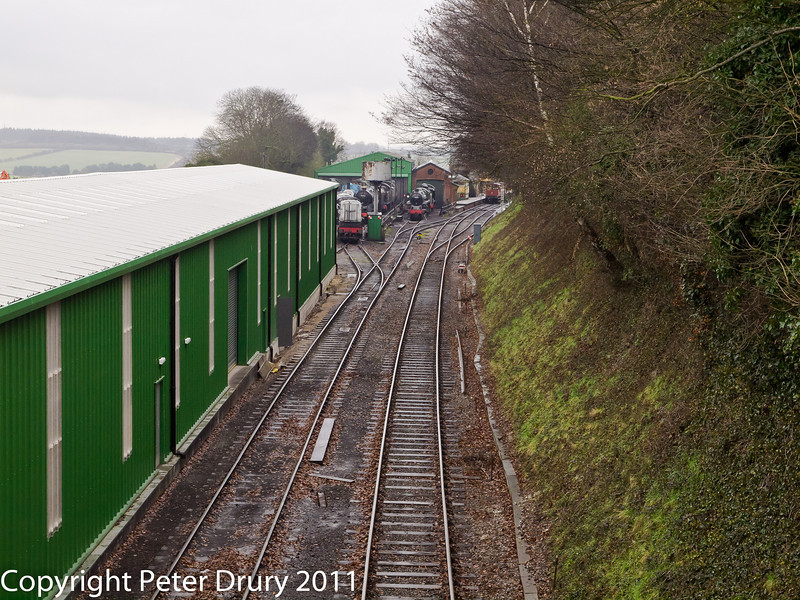 26 January 2011. Ropley:- Station approach from Meadstead & Four Marks.  Copyright Peter Drury 2011 The green building on the left is the re-built carriage and paint shop. The track (left foreground) is the link track for the workshop area and the start of the long storage siding. The right hand track is the main running line to/from Medstead & Four Marks. The large green building in the distance is the loco shed, the brick built building to its right is the wheel drop with the station platforms alongside.