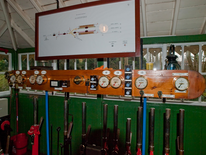 Alresford Signal Box. Copyright 2009 Peter Drury<br /> Here is another view of the indicator panel above the lever frame. All the necessary levers have been pulled and you will see that the needles on the two left hand dials (Outer Home and Inner Home) are now indicating to the right (OFF). All the others are pointing to the left (ON).<br /> The brass switch in the centre of the panel operates a bell which allows the signalman to alert the station staff of an incoming train.