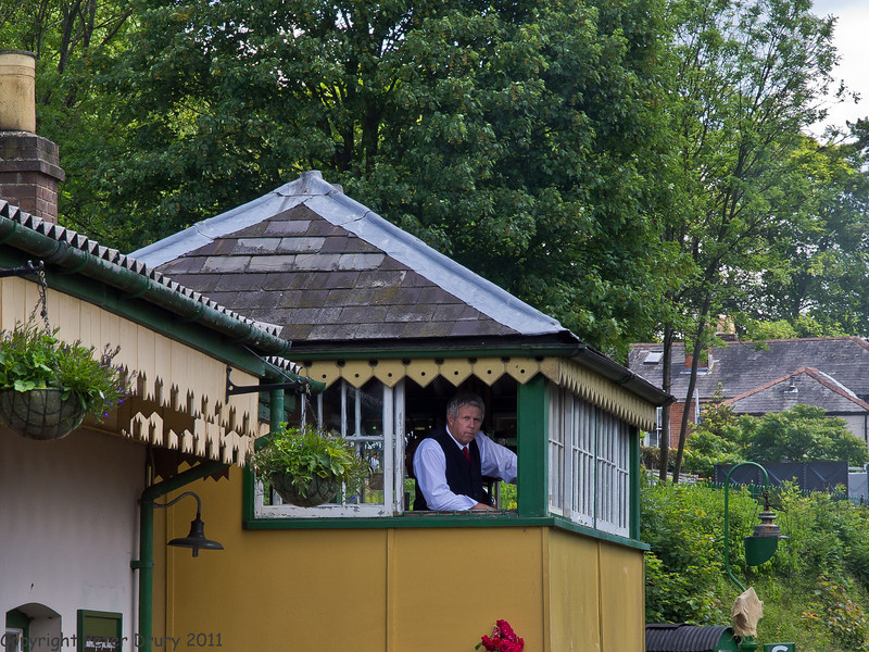 11 Jun 2011. War on the Line. Alresford Station Signal Box. The duty signaller is viewing the platform in readiness to give the Alton-bound train the right of way to Ropley. Copyright Peter Drury 2011