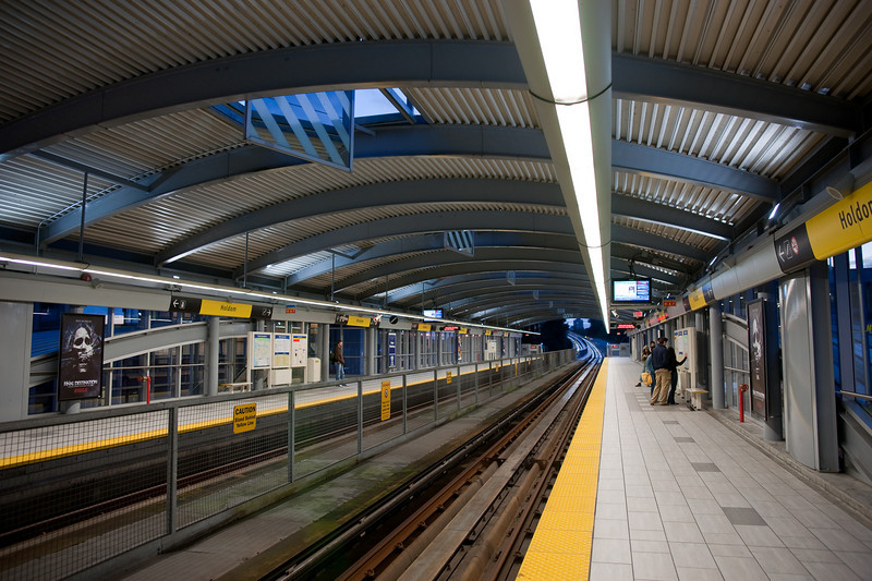 Holdom Station uses a single, graceful arch to connect the two platforms.  The station's public art uses mirrors set into square slots in the roof.