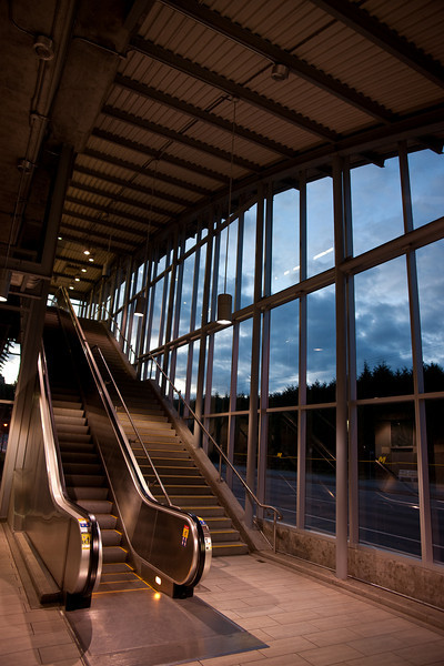 The escalator at Holdom Station.  Notice the graceful roofline and glass wall, providing a smooth transition from concourse to platform level.