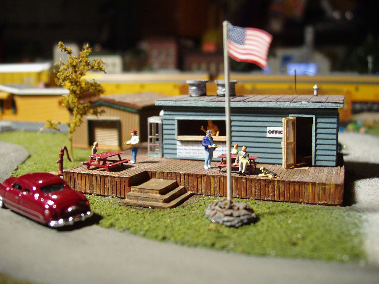 """This is the main office and snack bar for the """"Tinseltown Trailer Park"""".  The trailer park along with this """"kit bashed"""" building were my idea; the trailer park is located on """"the other side of the tracks"""" from the drive-in theatre.  """"Kit bashing"""" refers to taking parts from one or several existing model kits to create something different.  In this case I added the new wood-siding facade to an existing building, cut a hole in the side to create a snack bar counter, and added a REAL screen door (complete with tiny paper hinges so that it really opens and closes).  The """"Office"""" sign and """"Welcome"""" door mat were created using a laser printer and have text large enough to read, but the menu below the counter is just a bit too tiny for the printer resolution - and, thus, hard to make-out.  Items on the menu are movie themed; """"Ma and Pa Kettle Corn"""", """"From Here to Eternity Footlong Hotdog"""" and """"To Have and Have Not Brat""""  - available with or without sauerkraut, the sign says.  I just wish it could be read.  I added the phone booth and picnic tables, too - which are made from tiny folded pieces of metal (remember, this is 160th scale)."""