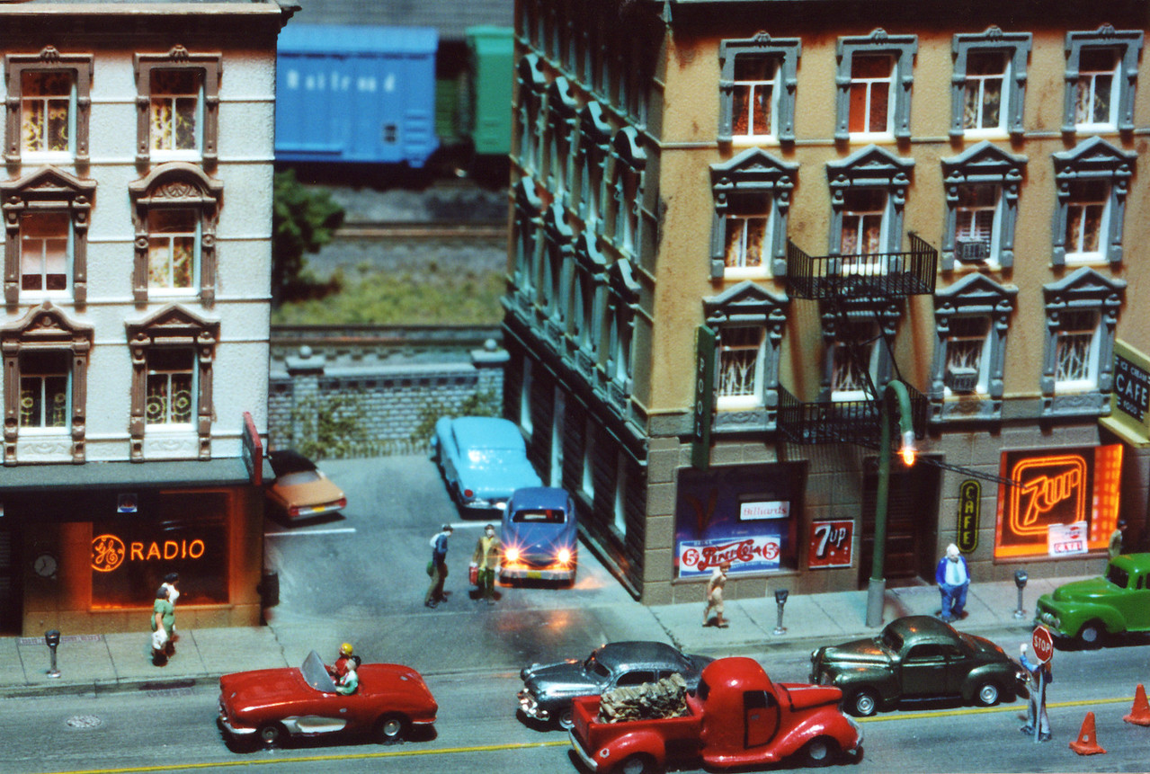 "This is a close-up of details on the N Scale city module. Note the working headlights on the car in the center of the scene, the working lamppost to the right, and the ""neon"" signs in the shop windows.  The neon effect is created by adding a light to the edge of a plastic window with a logo engraved into it."