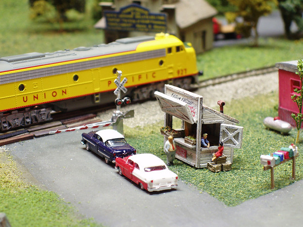 """I love this N Scale fruit stand.  I built it from a laser-cut wood kit.  It may be my favorite addition to any of my modules.  I came up with the idea of the owner """"chatting-up"""" a woman while a customer waits.  Typical.  ;^)"""
