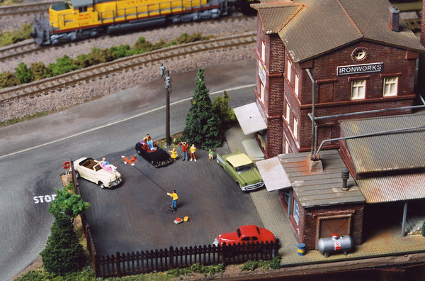"""The is one of my N Scale modules (the """"lock and dam"""" module) designed and built by Dale Blust.  His modules have many incredible, creative details.  Here a boy flies a model plane (which actually moves thanks to a motor hidden under the parking lot) while onlookers snap photos (a fiber optic camera flash occurs randomly)."""