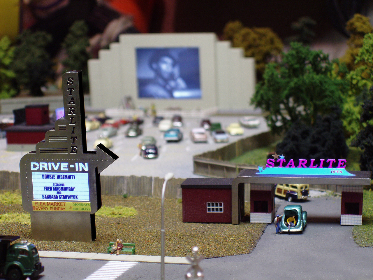 "My drive-in theatre in N Scale, created from a metal kit with an LCD TV as the movie screen.  The kit is great, but what makes the scene are all the ""extras"" that I added with the help of fellow modelers.  In this shot you can see someone getting caught trying to sneak in.  I have a real drive-in speaker next to the module that plays the audio from whatever movie is being shown.  The number of cars has grown since this photo was taken.  At a cost of about $5 per car, it took me a while to acquire enough cars to fill the parking lot!  One of my all-time favorite movies is showing... Walter: Suppose I bust out crying and put my head on your shoulder.  Phyllis: Suppose you try putting it on my HUSBAND'S shoulder."