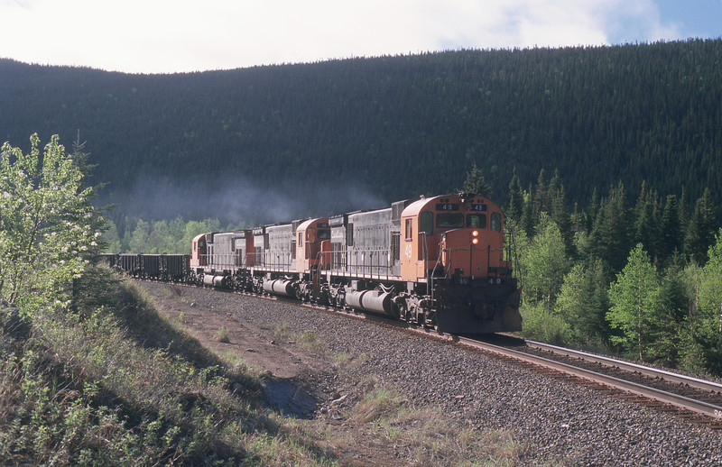 Early morning on May 30th and the sun was out. At MP 22.5 MLW 49 heads another trio of the six motor Centuries up country on empties for Fermont.