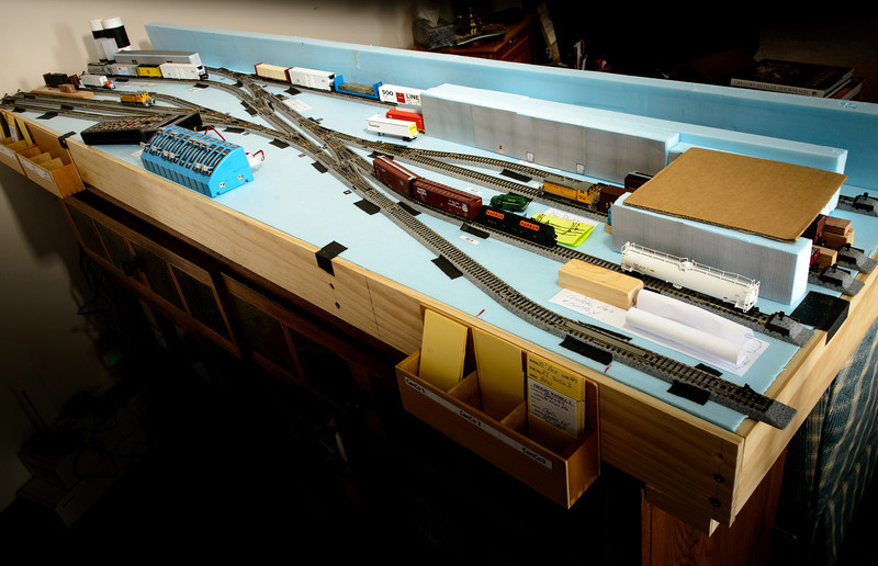 This small plan was inspired by an industrial area in Omaha.  A lot a license was taken to fit things into the narrow (18 inch) shelf.<br /> <br /> The scenery is mocked up from foam insulation, paper and wood pieces to experiment with sight lines and building placement.  No sense building a lot of structures to find out they should be a different size.<br /> <br /> The train layout overhangs the cabinet by a few inches on each end.  If you want to avoid this situation you should probably buy the cabinet first. Do ask how I know this.<br /> <br /> The track is temporarily held to the surface with gaffer tape.  Now that I'm sure of the final track plan I'll glue the track in place and start on the scenery.