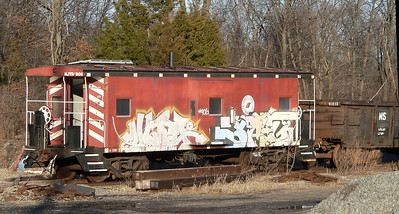 """Ex Erie C380, ex D&H 35817 bay window caboose. Now NJT 906 and shamefully """"tagged"""" at Campbell Hall, NY."""