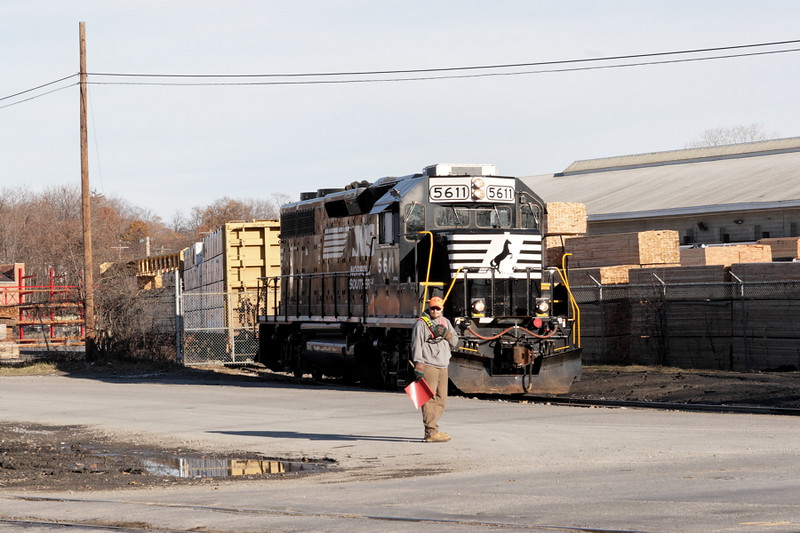 NS GP38-2 #5611 on the Rowley Lumber spur. The flagman is waiting to flag the crossing at Wisner Ave.