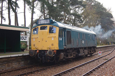 And 25057 is seen passing the passenger shelter on platform 2 at Holt.