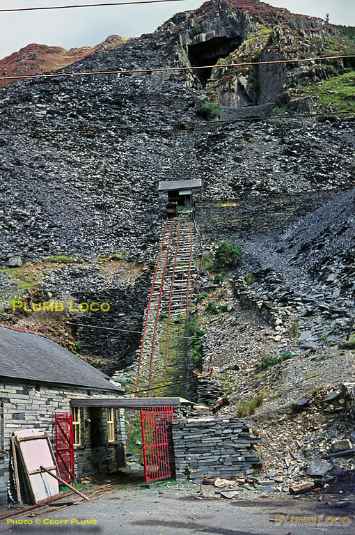 "Corris Railway. 1966/08/xx, 04. Aberllefenni Quarry was still in use at this time, though only through one adit to the left of the building at the bottom of the incline, the upper levels being closed. The 2' 3"" gauge tramway was still used to transport slate to the cutting sheds further down the valley near where the line originally connected to the Corris Railway. Latterly, there being no locomotives, farm tractors were used, straddling the track! August 1966. Slide No. 2384."