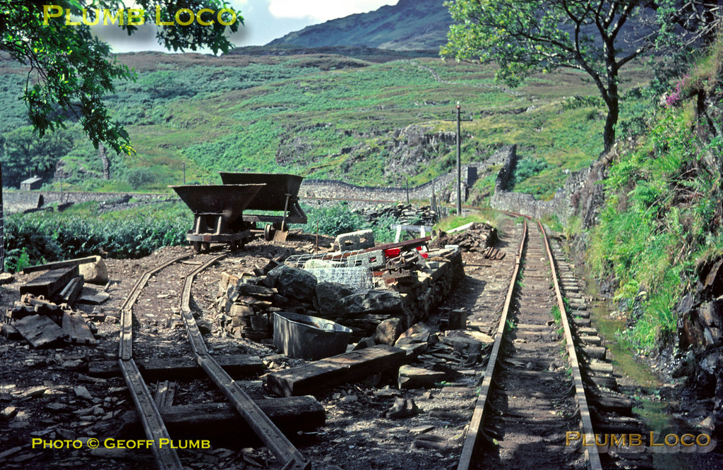 "Ffestiniog Railway. 1966/08/xx, 01. On the Ffestiniog Railway at Campbell's Curve/Platform, looking towards Tan-y-Bwlch. The line above Tan-y-Bwlch was still derelict at this time, though work was going on to reopen to Dduallt and initial work undertaken on the ""Deviation"" to get around the pumped storage scheme that blocked the route above Moelwyn Tunnel. Temporary track has been installed as part of the work to build the engineering platform. August 1966. Slide No. 2389."