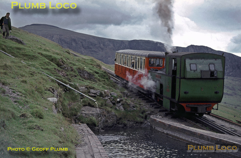 "Snowdon Mountain Railway. 1964/07/31. SMR No. 5 ""Moel Siabod"" sets off from Halfway station, passing the locally sourced water tank, on its way to the summit. Cloud has now cleared the tops of the mountain, though the summit itself cannot be seen from this point. The course of the railway can be seen higher up above the rock faces to the left of the train, climbing from left to right and over the horizon. Friday 31st July 1964. Slide No. 922."