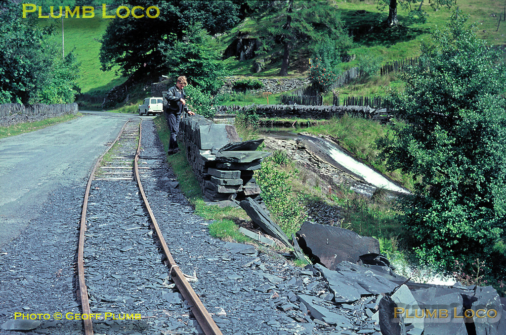 "Corris Railway. 1966/08/xx, 03. Part of the 2' 3"" gauge quarry line from Aberllefenni quarry to the cutting sheds was still in occasional use at this stage, originally the line also connected to the Corris Railway. The motive power used was a farm type tractor, straddling the rails! My brother Barry is standing by the slate wall in this view looking towards the quarry. August 1966. Slide No. 2382."