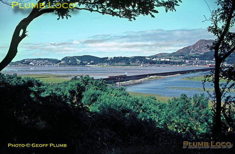 "Ffestiniog Railway. 1966/08/xx. Seen from the slopes above Boston Lodge Works area, Ffestiniog Railway No. 2 ""Prince"" is taking a short train across The Cob towards Porthmadog, nestling below Moel-y-Gest, the tide in the Glaslyn estuary fairly high. August 1966.Slide No. 2404."