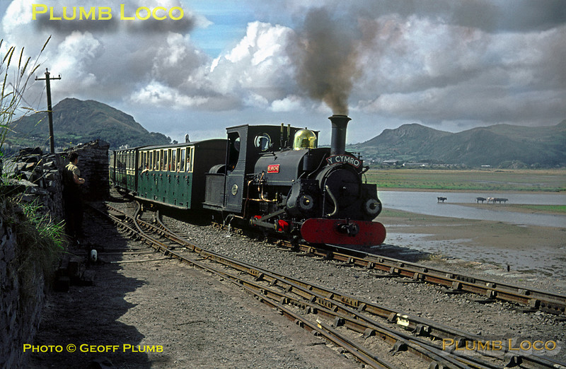 """Ffestiniog Railway. 1964/08/04. Ex-Penrhyn Railway 0-4-0STT """"Blanche"""" comes round the curve off """"The Cob"""" passing Pen Cob Halt and the trackwork into Boston Lodge Works and shed. She is in charge of """"Y Cymro"""" (""""The Welshman""""), the non-stop 15:00 train from Porthmadog Harbour to Tan-y-Bwlch on Tuesday 4th August 1964. Slide No. 962."""