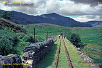 "Ffestiniog Railway. 1966/08/xx, 02. The section of the Ffestiniog Railway between Dduallt and Moelwyn Tunnel and on to Tanygrisiau station was abandoned after the reservoirs for the pumped storage scheme flooded the trackbed beyond the tunnel. This is the view looking towards the tunnel entrance from the Dduallt end. A new ""deviation"" line was built around the abandoned section, this now runs at a higher level to the left of this formation. August 1966. Slide No. 2395."