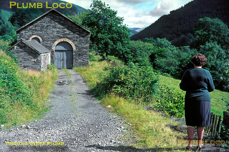 """Corris Railway. 1966/08/xx, 01. My mother Margaret takes in the scenery at the former Corris Railway engine shed at Maespoeth Junction during a family holiday in August 1966. The shed lay in the """"vee"""" between the Upper Corris Tramway to the left and the Corris main line to Aberllefenni to the right of the shed. Fortunately, the shed was used for other purposes for many years and survived to become once again the revived railway's engine shed. Slide No. 2379."""