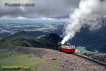 "Snowdon Mountain Railway. 1964/07/31. Almost at cloud level, SMR No. 2 ""Enid"" has just passed No. 6 ""Padarn"" at Clogwyn station loop, seen in the background, and is now slogging away on the final stretch to the summit as it crosses the embankment on the narrow ridge high above the Llanberis Pass. Llyn Padarn can be seen way below to the left of the picture. Friday 31st July 1964. Slide No. 913."