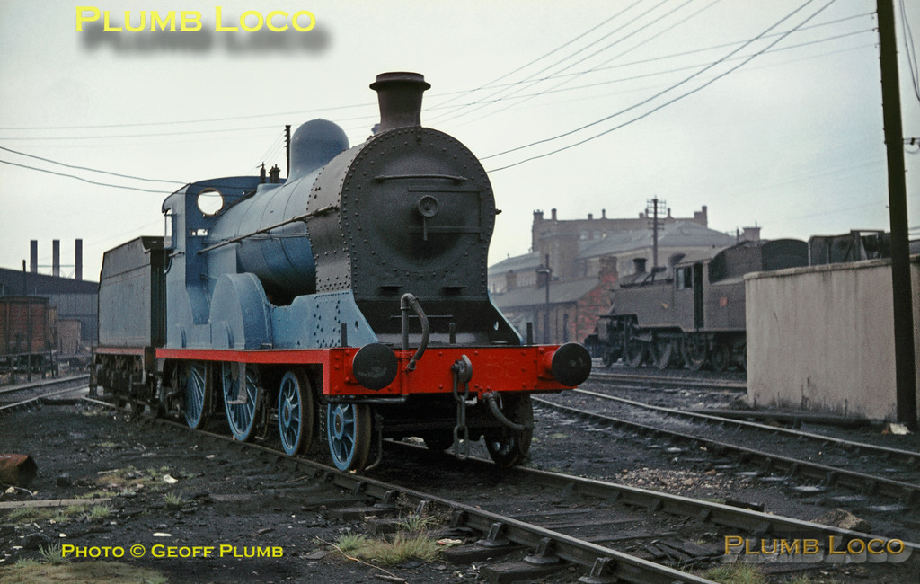 """Preserved ex-Great Northern Railway (Ireland) Class S 4-4-0 No. 171 """"Slieve Gullion"""" (Beyer, Peacock No. 5629/1913) had just undergone an overhaul at Harland & Wolff and is still in undercoat for its blue livery at Belfast York Road depot. The tender has also still to be repainted and will require turning before re-coupling to the engine! No. 171 was later based at the RPSI depot at Whitehead. In the background is one of the 18 """"WT"""" Class 2-6-4T's (known as """"Jeeps"""") built by the LMS at Derby from 1946 for the Northern Counties Committee, designed by Ivatt but similar to the Fowler 2-6-4T. September 1968. Slide No. 3448."""