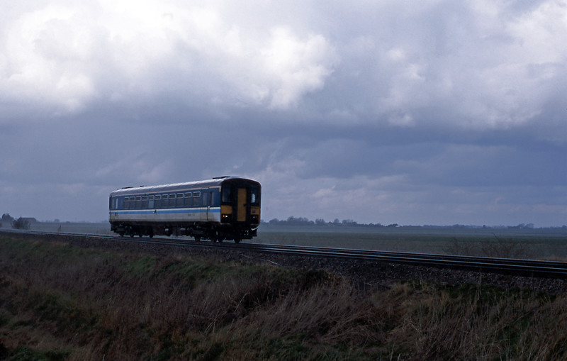 Tin Rockets have been banished from AGA's Peterborough to Ipswich service, but here's one still in Regional Railways livery passing Welney Road Crossing, Manea
