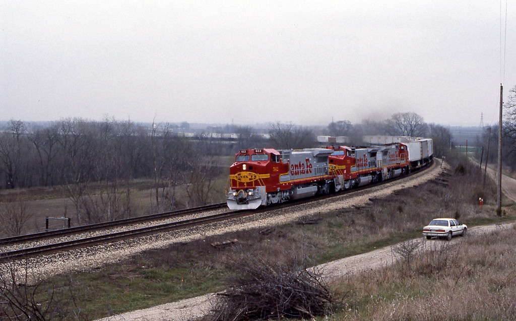 Ascending the hill from Chillicothe a Santa Fe piggyback train headed by 562 a B40-8W
