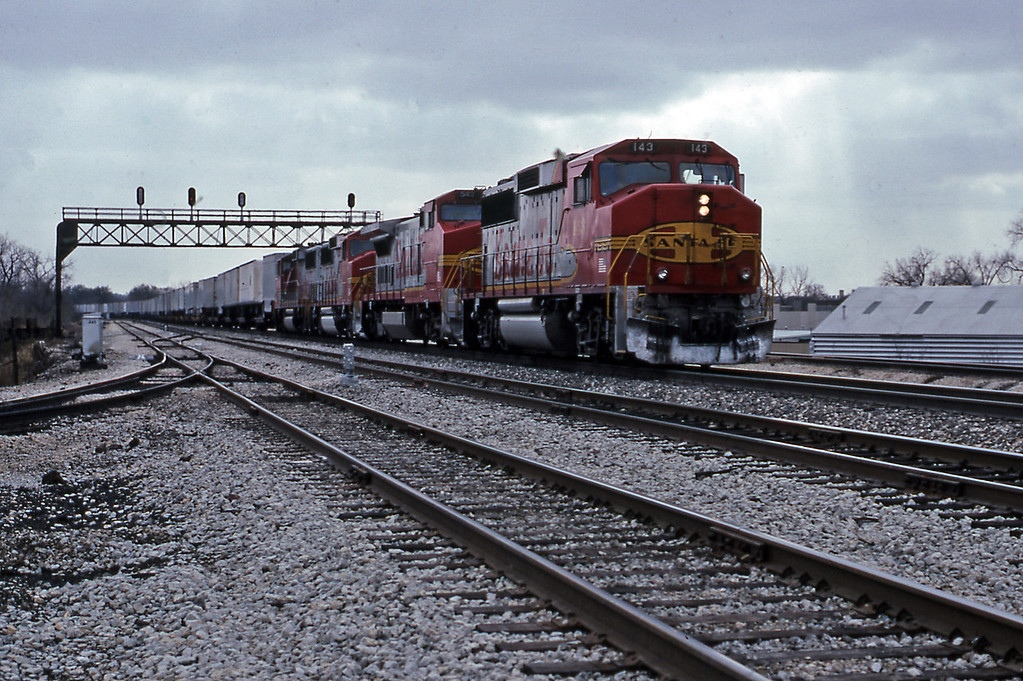 A Santa Fe eastbound piggyback bound for Corwith Yard passing Joliet, behind four warbonnet units led by GP60M 143. By now the cold drove me back to Chicago on the next Rock Island District train.