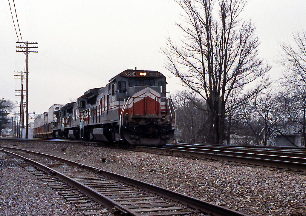 I was making my way towards Naperville to meet up with Mel Finzer, but stopped en-route at Rochelle where the BN Twin Cities mainline crosses the CNW overland route. On the BN a trio of the LMX units on a double stack crossing the CNW.
