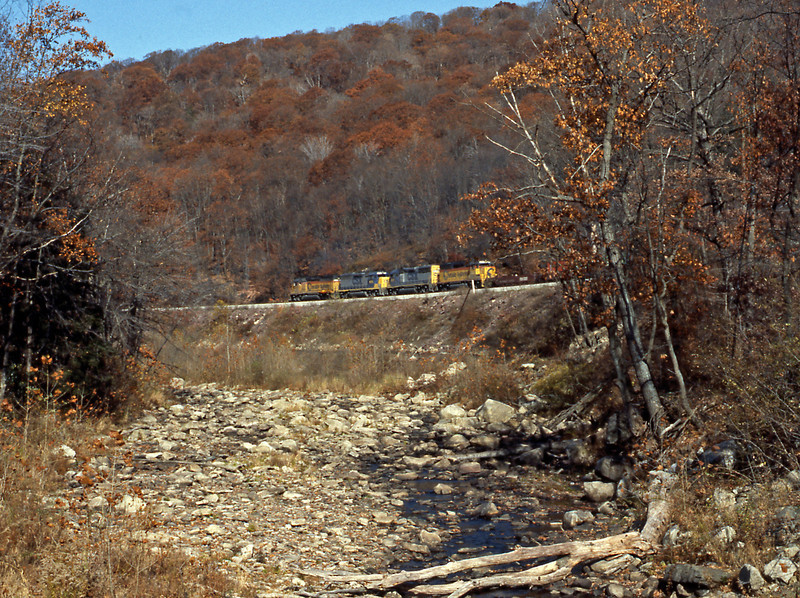 After the excitement of the Capitol I drove up to Hyndman, Pa. on the ascent to Sandpatch Summit. It was pleasantly warm in the autumnal sun. I seem to remember that I had to wait for some time before the distant sound of labouring diesels could be heard. Running along Wills Creek four EMD GP40-2s head west with an empty double stack