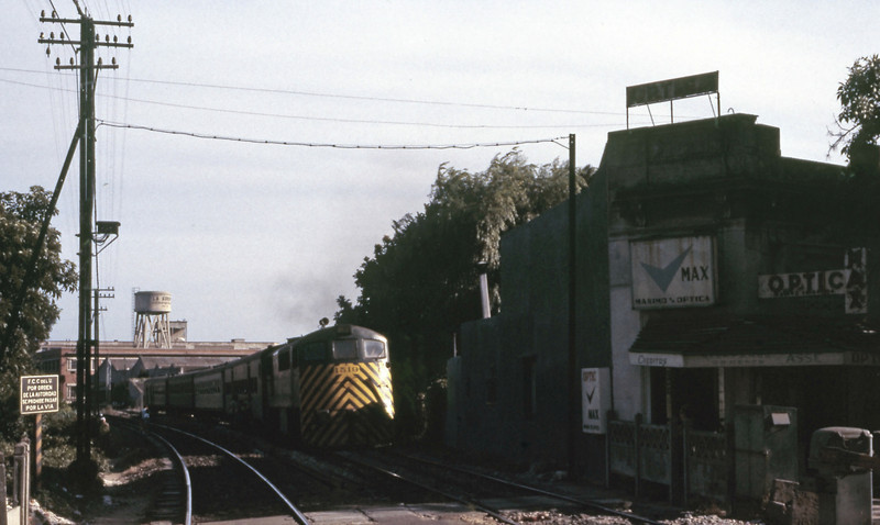 Evening shadows over the line a couple of miles north of Central station as a 1500 heads towards Sayago and Penarol. The old Central Uruguay Railway sign warning locals not to walk on the lines is ignored by everyone.