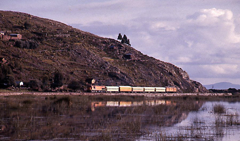 The overnight train from Arequipa approaching Puno along the shores of Lake Titicaca a few days after Christmas 1984, the second car is the wooden bodied sleeping car dating back to the 1920s.