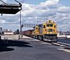 A westbound Santa Fe freight behind 6403, a B23-7 passing Joliet's westbound platform