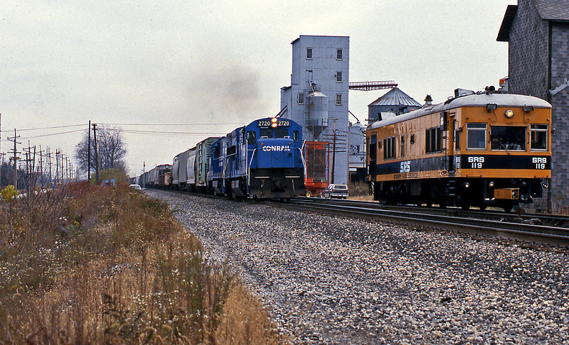 From Hudson Lake to South Bend the South Shore parallels the New York Central Water Level Route. In 1987 New Carlisle was a flagstop on the interurban, which was closed in 1990. A Conrail merchandise train passing a Sperry track recording car, 2720 is a former PC GE U23B.