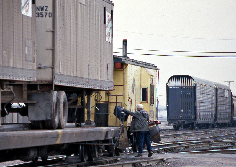 The conductor or brakeman throws his bags on board the caboose as the train leaves the yard.