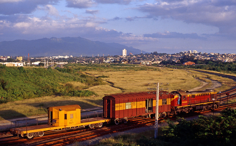 Early evening sun in Santiago. this is on the new alignment, 71026 has finished its work for the day and is heading off towards the harbour. The new station train shed can be seen above the crew car and below the large white building on the skyline, train 14 is ready to leave.