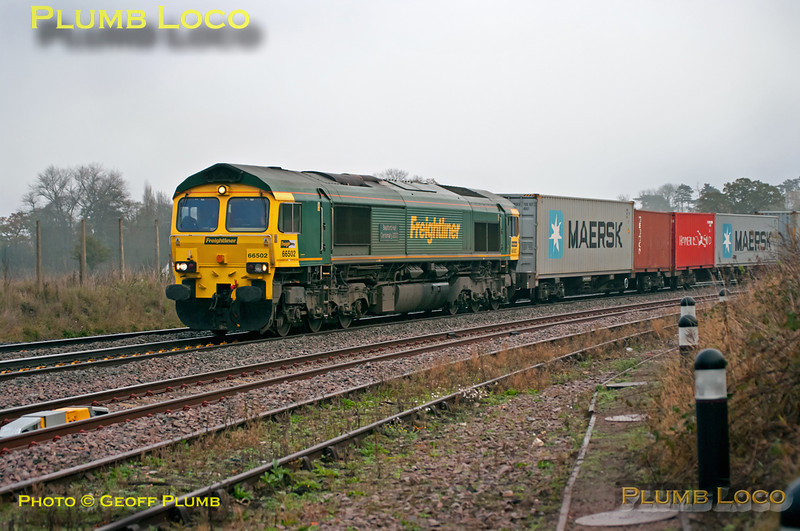 """The weather on Saturday 19th November 2011 varied widely around the country with some places in thick fog, some in bright sunshine and others just dull... In the dull category was  Shustoke foot-crossing just east of Whitacre Junction where Freightliner 66502 """"Basford Hall Centenary 2001"""" is heading west with 4M88, the 03:52 from Felixstowe to Lawley Street at 09:05. Digital Image No. GMPI10610."""