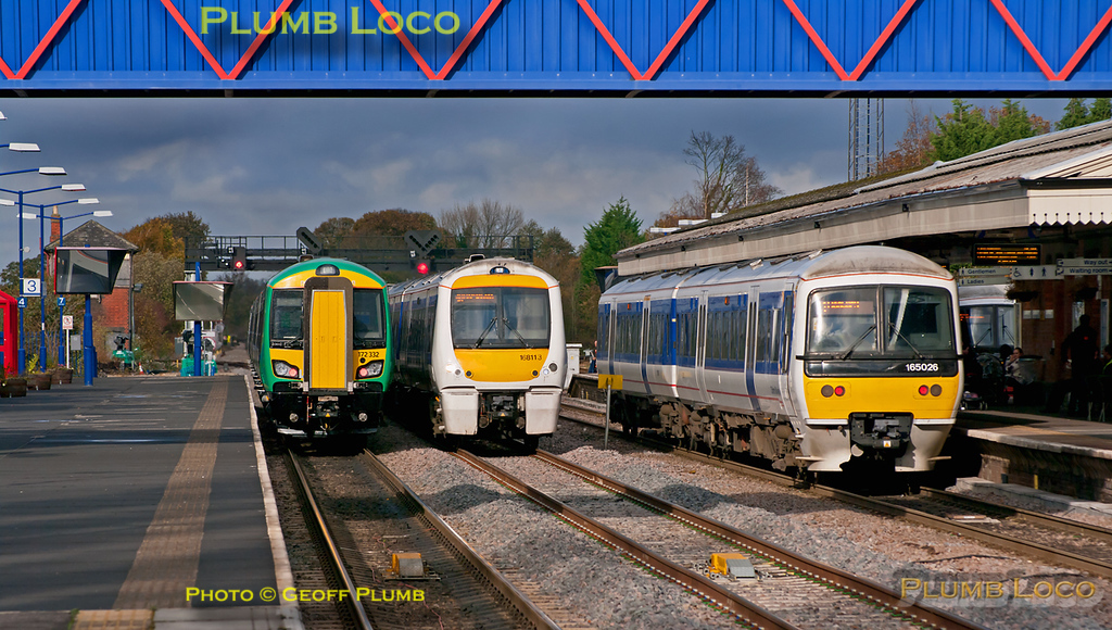 "All four tracks at Princes Risborough occupied once again! On the left is London Midland 172 332, together with 172 221, running mileage accumulation turns. This is 5Z02, 12:56 from High Wycombe to Dorridge and it has been stopped in the station to allow a northbound Chiltern non-stop service to overtake. It would normally have been put into the centre road but this was required for the passage of 168 113, here seen southbound with the 11:55 from Birmingham Moor Street to Marylebone. On the right is 165 026 with the 12:13 from Marylebone to Banbury which arrives here at 12:57 and departs at 13:10 after the northbound non-stopper has passed. An unidentified 165 is also just visible in the bay with the Aylesbury shuttle. The 172s have the shunt signal ""off"" to put them on to the stub of the Thame branch to get them out of the way and the train had pulled forward but stopped short of the signal as this move was cancelled. The northbound non-stop was then put through on the centre road... 13:07, Friday 4th November 2011. Digital Image No. GMPI10551."