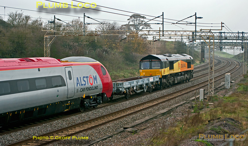 Colas Rail 66744 is in charge of 6X39, the 05:37 from Dollands Moor to Edge Hill, hauling newly delivered eleven car Pendolino 390 055 with a barrier wagon in between. It is passing Old Linslade on the down slow line at 09:07 on Wednesday 16th November 2011, another very dull morning. Digital Image No. GMPI10607.