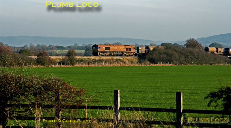 With a backdrop of the Chiltern hills, the Chiltern lines RHTT, 3J04, is working the Sunday leg between Princes Risborough and Bicester North, seen near Kingsey, south of Haddenahm. A pretty dirty 66001 is leading the train, an even filthier 66017 was bringing up the rear, out of this shot. 12:30, Sunday 13th November 2011. Digital Image No. GMPI10570.