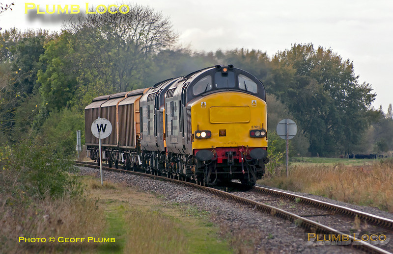 DRS Class 37s Nos. 37611 and 37601 have been on hire to DBS and substituted for Class 66s on several workings. This is 6A49, the 12:10 from Didcot Yard to Bicester MoD depot, approaching the level-crossing at Islip at 12:35 on Thursday 13th October 2011, just as the sun disappeared... Digital Image No. GMPI10392.
