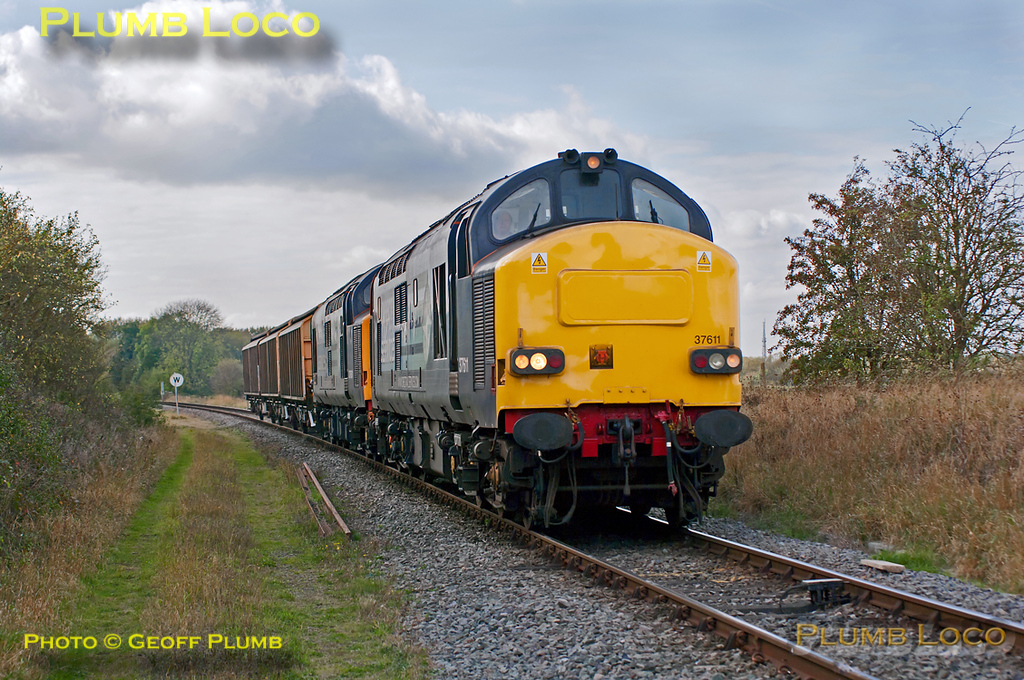 DRS Class 37s Nos. 37611 and 37601 have been on hire to DBS and substituted for Class 66s on several workings. This is 6A49, the 12:10 from Didcot Yard to Bicester MoD depot, approaching the level-crossing at Islip at 12:35 on Thursday 13th October 2011, just as the sun disappeared... Digital Image No. GMPI10399.