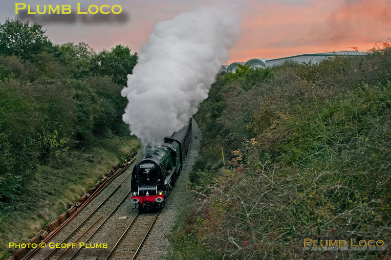 """With the setting sun tingeing the sky, Stanier """"Princess Coronation"""" class 4-6-2 No. 46233 """"Duchess of Sutherland"""" is getting away from the stop for water at Ridgmont station with 1Z87, the 16:13 return from Euston to Sheffield, 17:42, Saturday 20th October 2012. The huge warehouse on the right is on the site of the former brickworks on the Marston Vale line. Digital Image No. GMPI12696."""