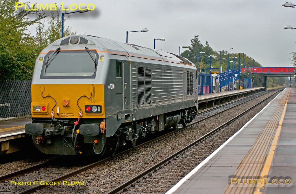 """On a wet and miserable Monday 8th October 2012, former WSMR 67010 returned from Crewe IEMD to Wembley LMD running as 0Z10, 09:55 from Crewe, to take up its place with Chiltern Railways. It had been out of action since before the demise of Wrexham & Shropshire (who had possible plans to name the loco """"Charles Darwin""""), so it was good to see it again on """"home turf"""" as it passes Haddenham & Thame Parkway station at 13:43. Digital Image No. GMPI12526."""