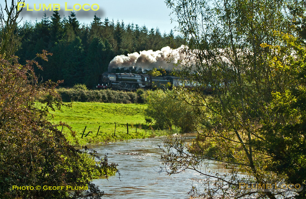 "The River Evenlode is in full spate in one direction while ""Britannia"" 4-6-2 No. 70013 ""Oliver Cromwell"" is in full cry in the other direction. It is working hard at the head of 1Z71, ""The Cotswold Venturer"", 08:05 from Paddington to Worcester via Evesham and return via Sapperton on Saturday 6th October 2012. In glorious, but awkwardly angled, sunlight the train is seen near Lyneham running on time at 11:06. Digital Image No. GMPI12508-2."