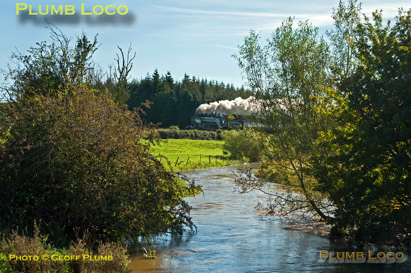 """The River Evenlode is in full spate in one direction while """"Britannia"""" 4-6-2 No. 70013 """"Oliver Cromwell"""" is in full cry in the other direction. It is working hard at the head of 1Z71, """"The Cotswold Venturer"""", 08:05 from Paddington to Worcester via Evesham and return via Sapperton on Saturday 6th October 2012. In glorious, but awkwardly angled, sunlight the train is seen near Lyneham running on time at 11:06. Digital Image No. GMPI12508."""