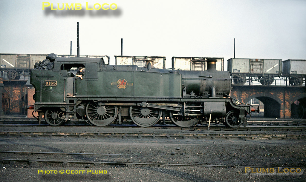 GWR 61xx Class 2-6-2T No. 6135 has presumably had attention fairly recently at Swindon Works and been repainted in unlined green livery,which still looks fairly smart. It is standing in front of the ramp up to the coaling stage, which is full of 16 ton coal wagons, at Old Oak Common MPD and has just had its bunker filled with coal - some of the lumps look as though they will take a bit of manipulating to get them through the firehole door! Saturday 26th October 1963. Slide No. 444.