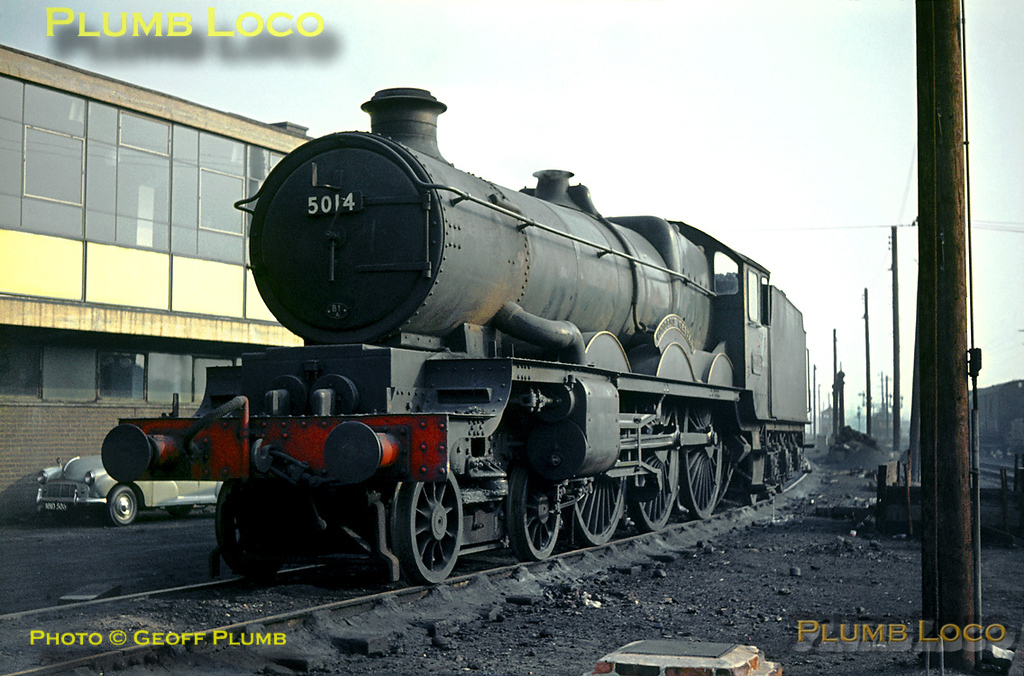 "GWR ""Castle"" Class 4-6-0 No. 5014 ""Goodrich Castle"" is allocated to 81A, Old Oak Common MPD, and is here at its home depot, simmering in front of the then new amenities block on Saturday 26th October 1963. I think the amenities block is still there, though the chances of seeing a ""Castle"" and the Morris (?) car in front of it are few and far between. Slide No. 445."