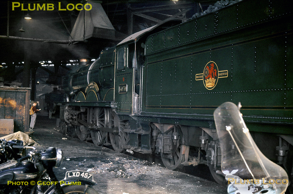 "Various staff motorcycles are in the foreground of this picture of still well cared for GWR ""Castle"" Class 4-6-0 No. 5070 ""Sir Daniel Gooch"", simmering inside the cavernous roundhouse that was Old Oak Common shed. A spotter notes down the number of the ""Castle"", while lurking in the background is a large GWR 0-6-0PT. Saturday 26th October 1963. Slide No. 443."